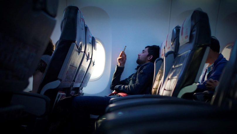 man checking phone on a plane